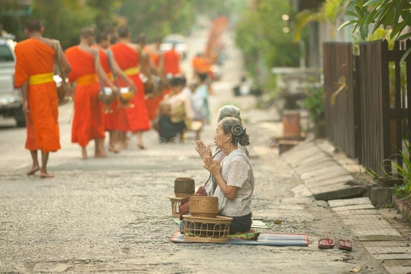 Povos que dão a esmola às monges budistas na rua, Luang Prabang, o 20 de junho de 2014 fotografia de stock