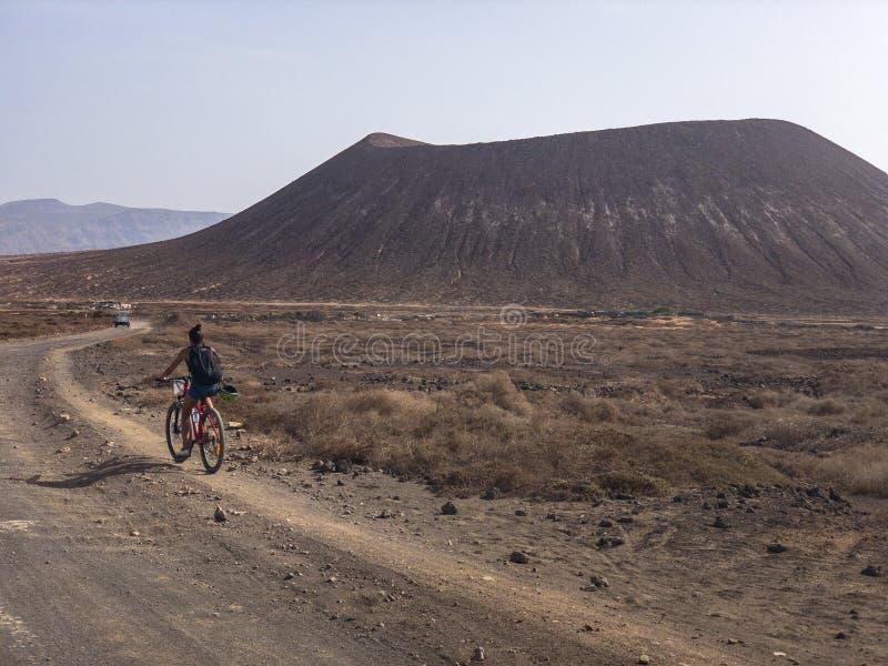Povos que dão um ciclo em um trajeto da sujeira na ilha do La Graciosa, Lanzarote, Ilhas Canárias fotos de stock