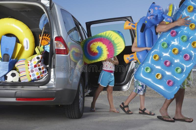 Povos que descarregam acessórios da praia do carro imagem de stock royalty free