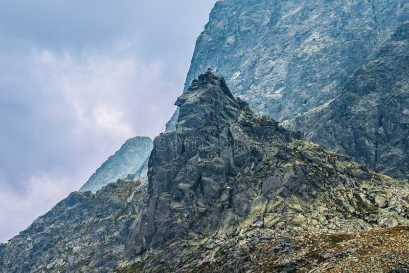 Povos que escalam à parte superior da montanha imagens de stock royalty free