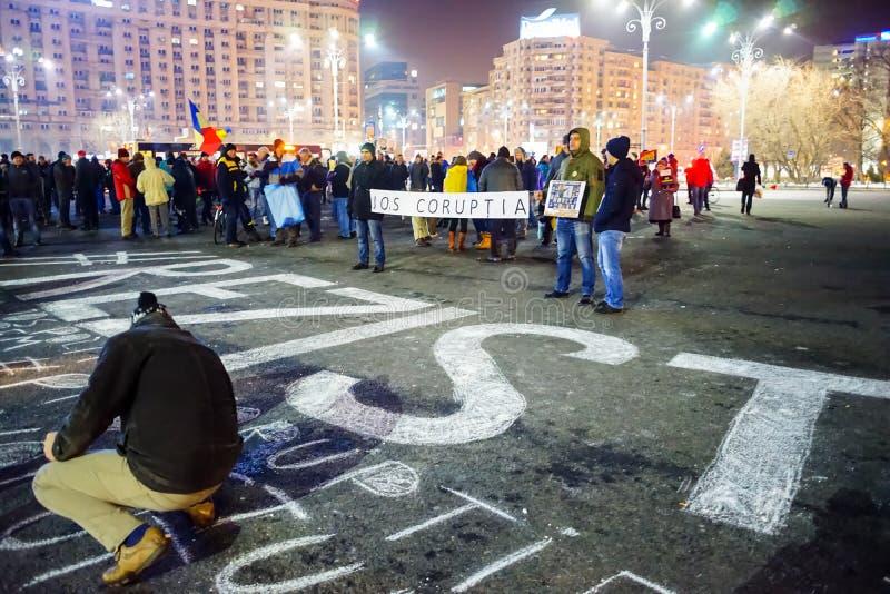Povos que escrevem a mensagem no concreto no protesto, Bucareste, Romênia imagem de stock royalty free