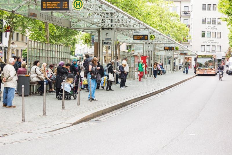 Povos que esperam o ônibus na parada do ônibus em Friedensplatz imagem de stock royalty free