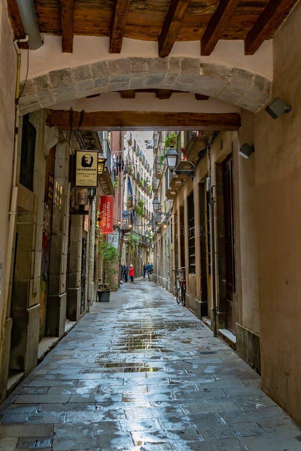 Povos que estão e que falam dentro de uma aleia em uma área de propriedades residenciais e comerciais em Barcelona fotografia de stock