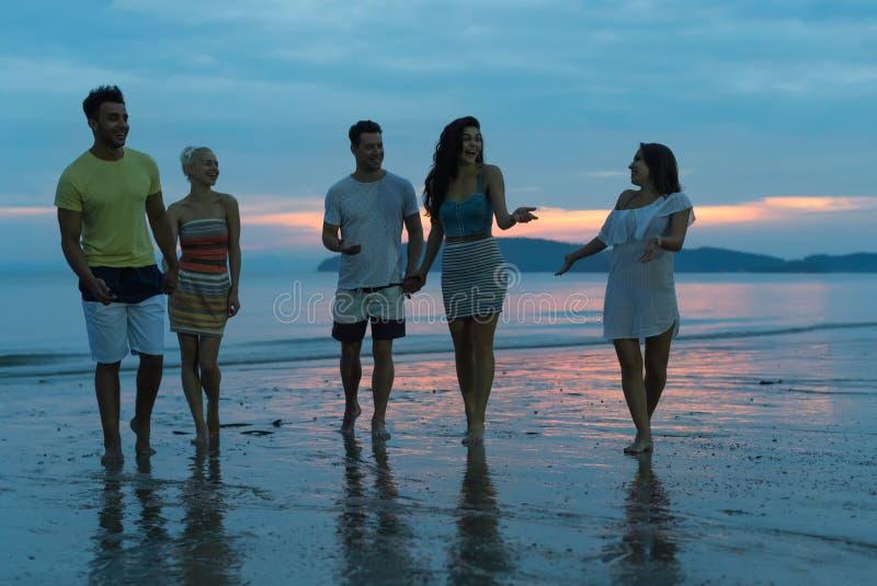 Povos que falam na praia no por do sol, grupo novo do turista que anda no mar em uma comunicação da noite foto de stock royalty free