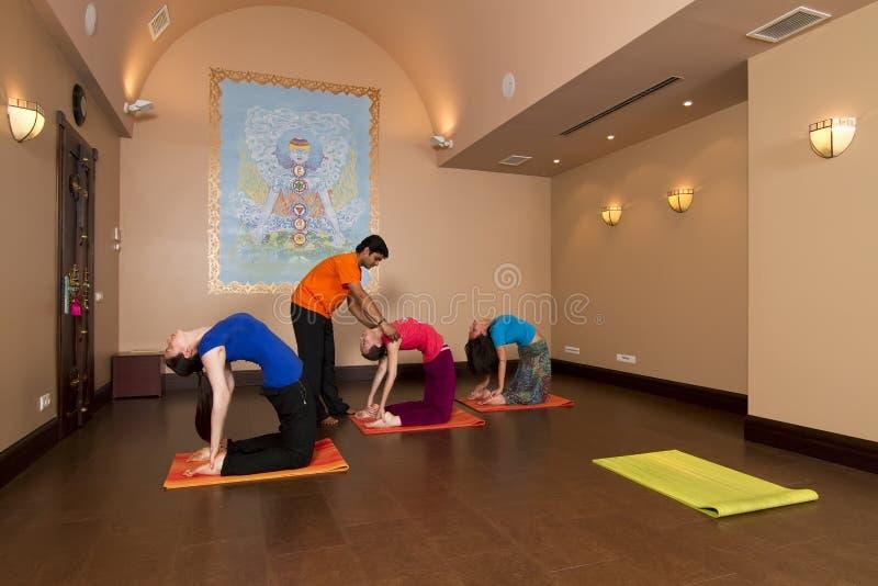 Povos que fazem a ioga no salão fotos de stock royalty free
