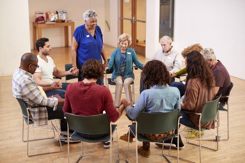 Povos que guardam as mãos e que rezam na reunião de grupo do estudo da Bíblia no centro comunitário imagem de stock