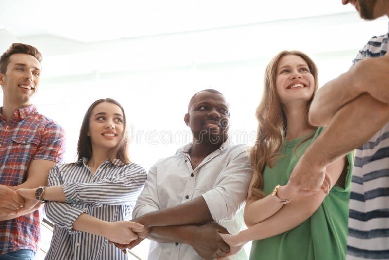 Povos que guardam as mãos no fundo claro Conceito da unidade imagens de stock royalty free