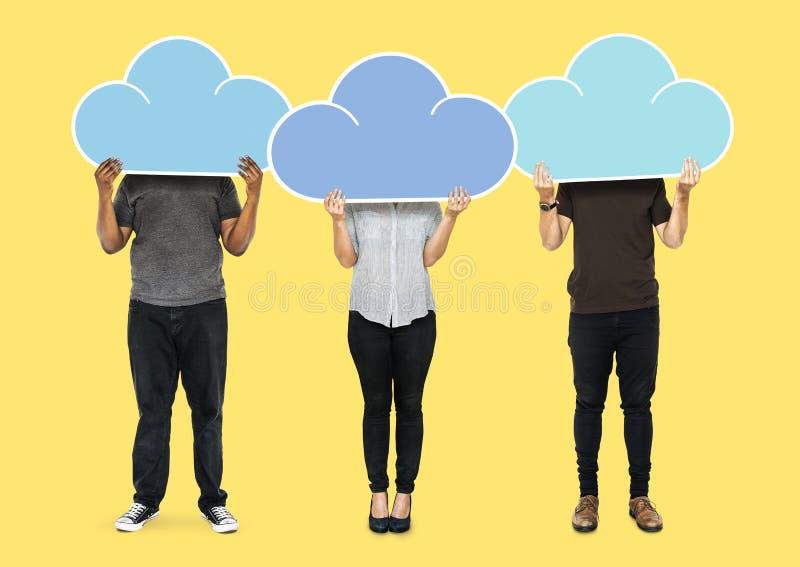 Povos que guardam símbolos do armazenamento da rede da nuvem foto de stock