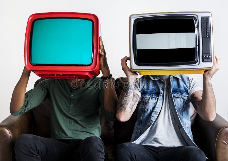 Povos que guardam a televisão retro próximos um do outro imagens de stock royalty free