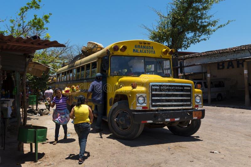 Povos que inscrevem um ônibus público velho em Granada, Nicarágua imagens de stock royalty free