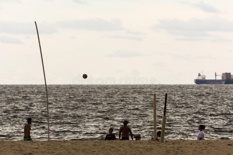 Povos que jogam o futebol na praia no por do sol, em Copacabana, Rio de janeiro, Brasil foto de stock