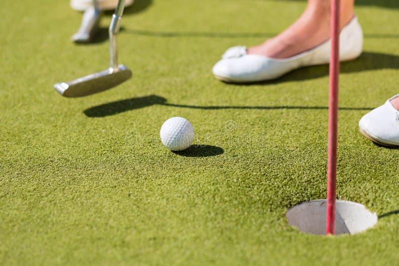 Povos que jogam o golfe diminuto ao ar livre foto de stock royalty free