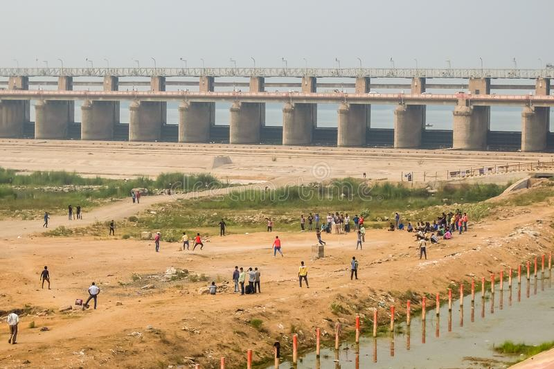 Povos que jogam o grilo no riverbank do rio de Krishna em Vijayawada Barragem de Prakasam no fundo imagens de stock royalty free