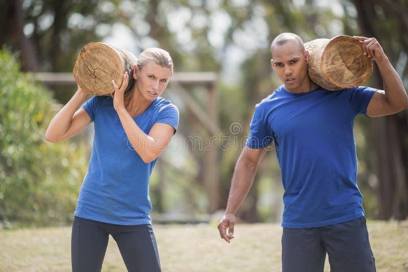 Povos que levam logs de madeira pesados durante o curso de obstáculo fotografia de stock royalty free