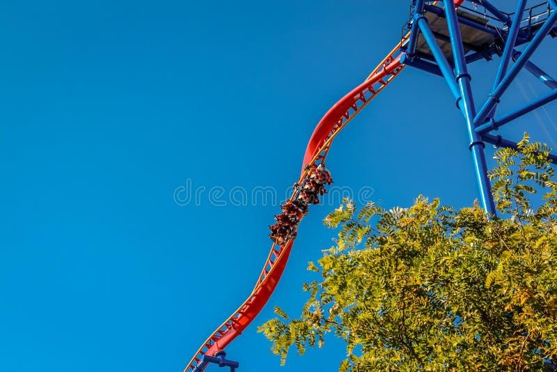 Povos que montam um roller coaster de aço de torção assustador em um parque de diversões fotos de stock royalty free