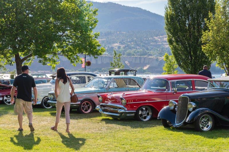 Povos que olham carros do vintage no parque na feira automóvel foto de stock royalty free