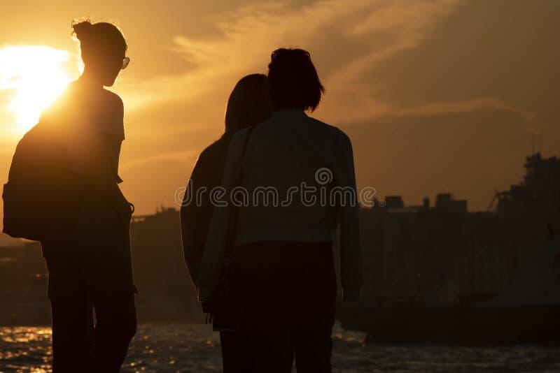 Povos que olham o por do sol e o mar fotos de stock