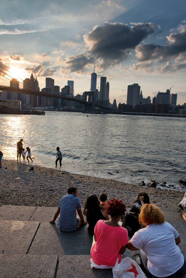 Povos que olham o por do sol sobre New York imagem de stock