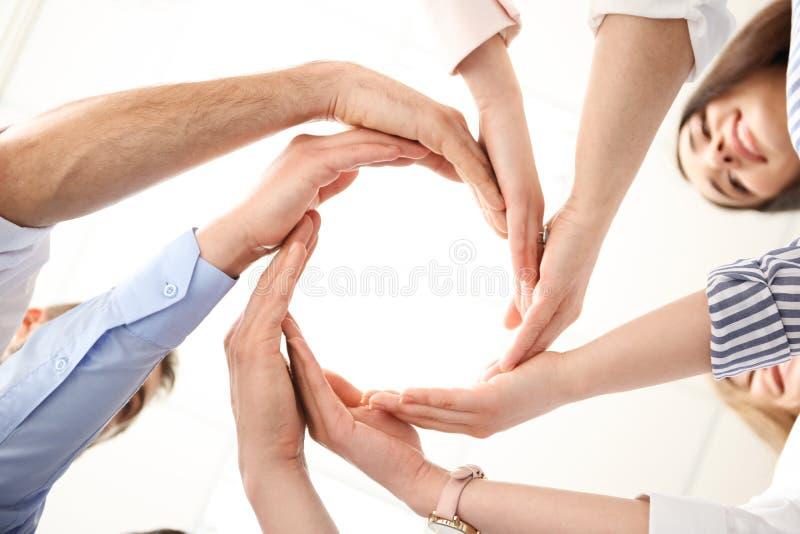 Povos que põem suas mãos no círculo imagens de stock royalty free