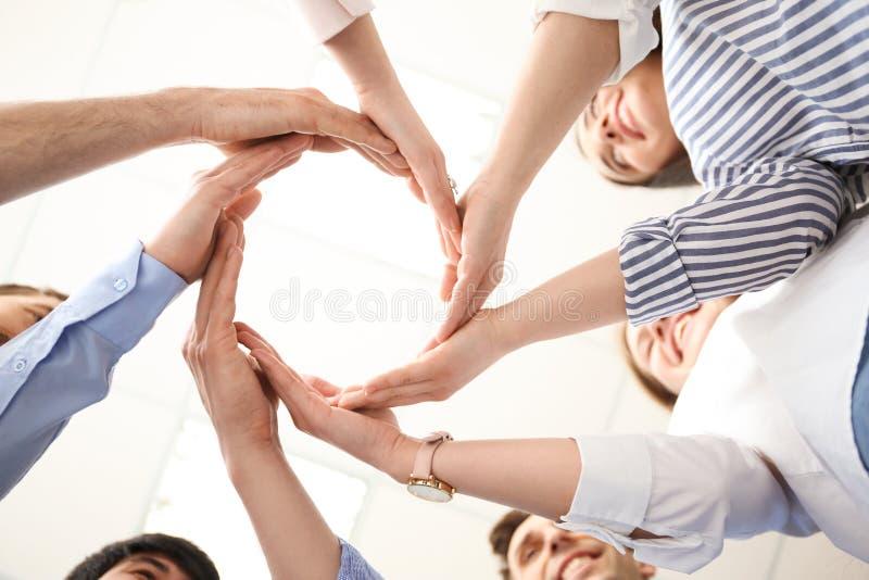 Povos que põem suas mãos no círculo imagem de stock royalty free