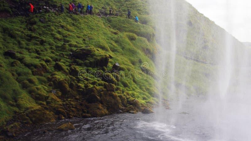 Povos que passam atrás da cachoeira de Seljalandsfoss fotografia de stock royalty free
