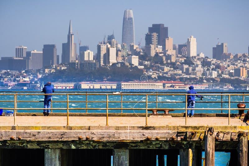 Povos que pescam de um dos cais que enfrentam a baixa de San Francisco; a skyline financeira do distrito da cidade visível no foto de stock