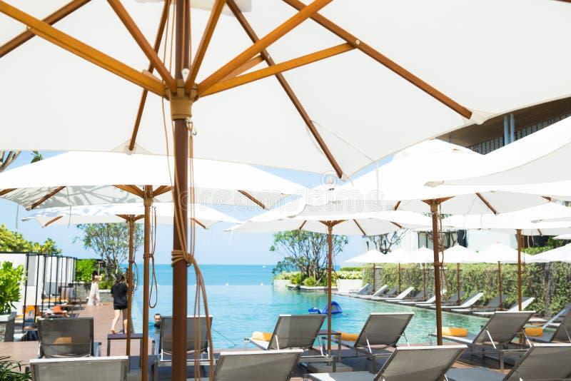 Povos que relaxam e para apreciar uma piscina luxuosa da infinidade no hotel da praia imagens de stock royalty free