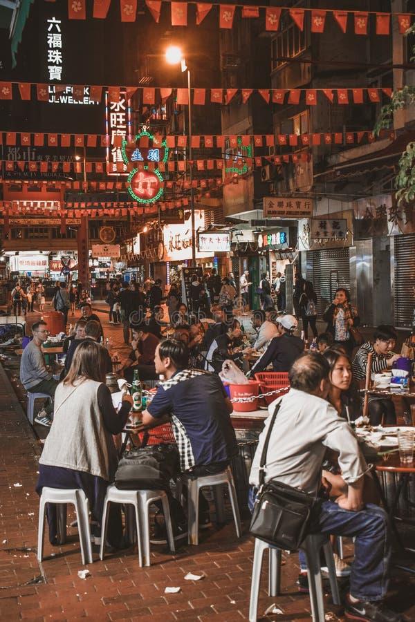 Povos que sentam e que comem o alimento da rua no mercado de rua de nivelamento do templo em Hong Kong imagens de stock