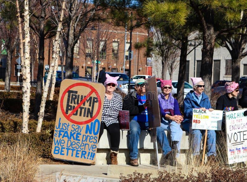 Povos que sentam-se com sinais e chapéus do bichano no ` s março Tulsa Oklahoma EUA 1 - 20 - 2018 das mulheres fotos de stock royalty free