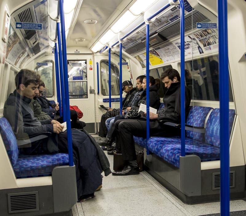 Povos que sentam-se dentro do trem subterrâneo do tubo de Londres imagens de stock