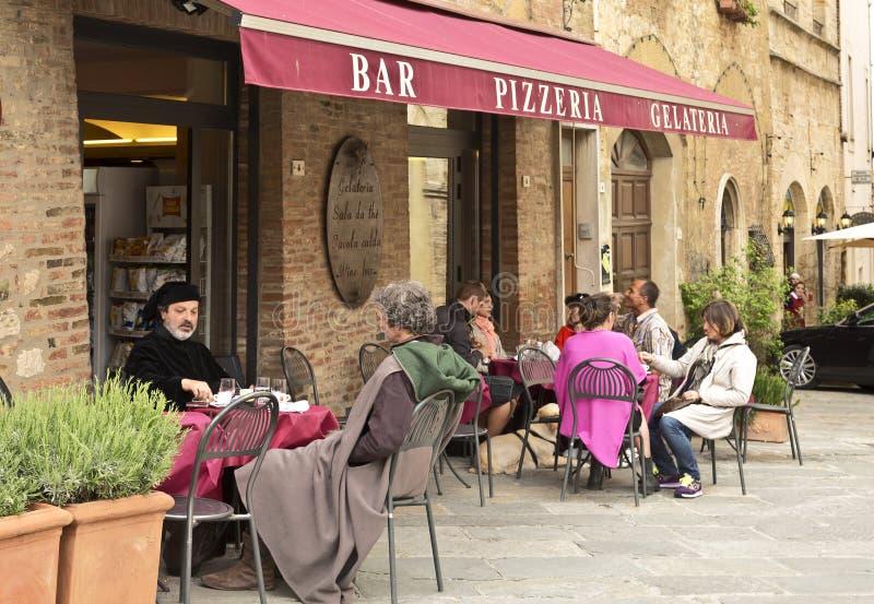 Povos que sentam-se em um café pequeno fora na cidade medieval de Montepulciano imagens de stock royalty free