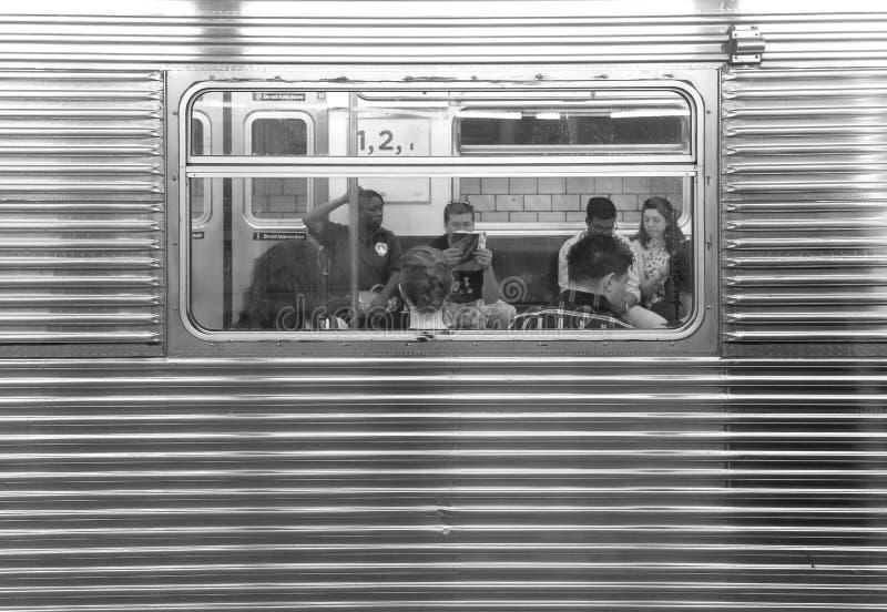 Povos que sentam-se em um carro de metro visto através da janela imagem de stock royalty free