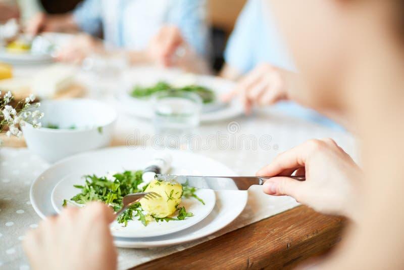 Povos que sentam-se na tabela e em comer fotografia de stock