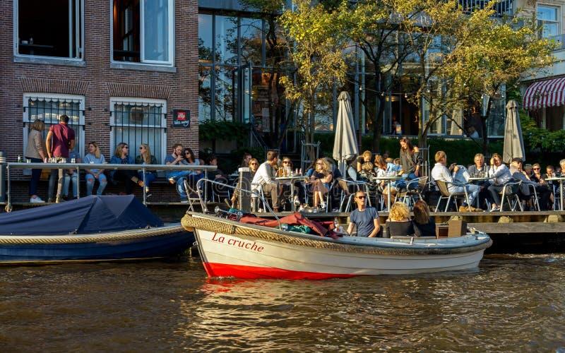 Povos que sentam-se no restaurante do café no canal em Amsterdão com o barco pequeno estacionado da excursão da cidade, os Países fotografia de stock royalty free