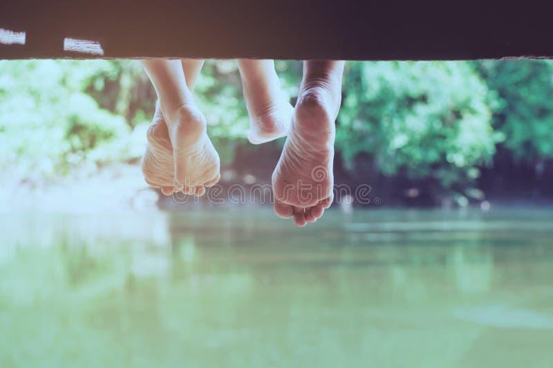 Povos que sentam-se para relaxar no cais sobre o rio fotografia de stock royalty free