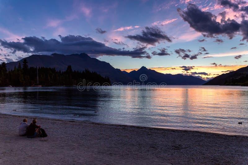 Povos que sentam-se pelo lago Wakatipu e pelo por do sol bonito de observação em Queenstown foto de stock royalty free