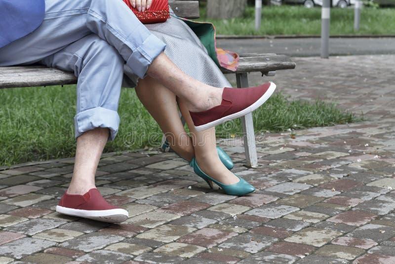 Povos que sentam-se, roupa elegante, banco de parque em um cit moderno imagem de stock royalty free