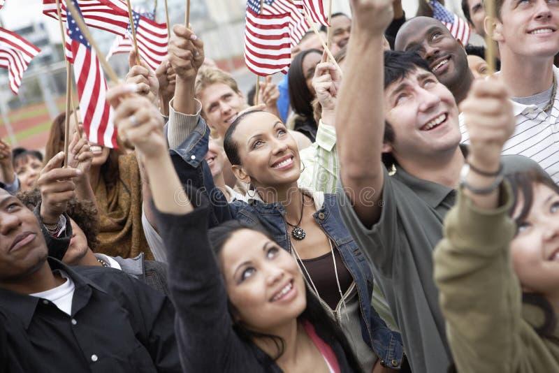 Povos que sustentam bandeiras americanas imagem de stock