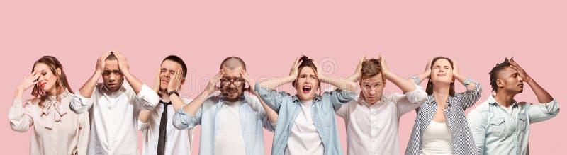 Povos que têm a dor de cabeça Isolado sobre o fundo cor-de-rosa foto de stock