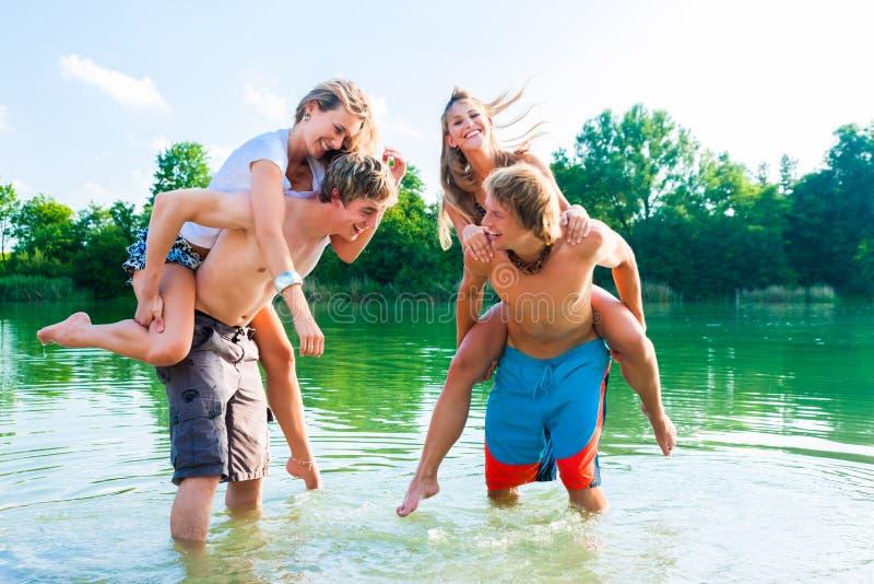 Povos que têm o divertimento no lago no verão imagens de stock