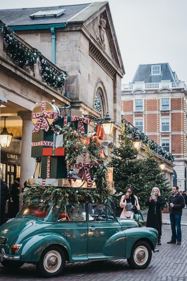 Povos que tomam fotos de decorações do Natal no mercado de Covent Garden, Londres, Reino Unido fotografia de stock royalty free
