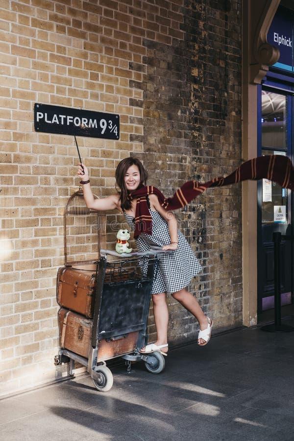 Povos que tomam a fotos por 9 3/4 de plataforma dentro da estação da cruz do ` s do rei, Londres, Reino Unido imagem de stock