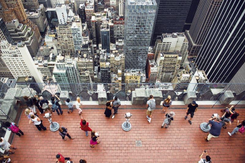 Povos que tomam imagens do telhado no arranha-céus de Manhattan fotografia de stock royalty free