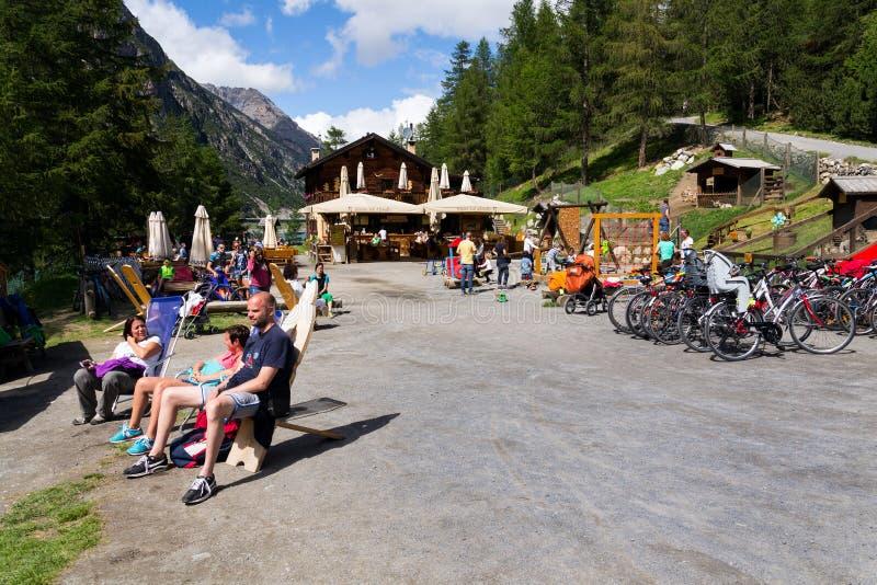 Povos que tomam sol na frente do restaurante com jogo de crianças e de bicicletas no banco de Lago di Livigno em Livigno, Itália imagem de stock royalty free