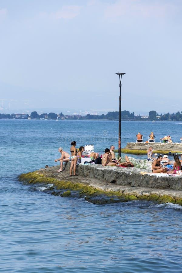 Povos que tomam sol na praia o 30 de julho de 2016 em Desenzano del Garda, Itália foto de stock