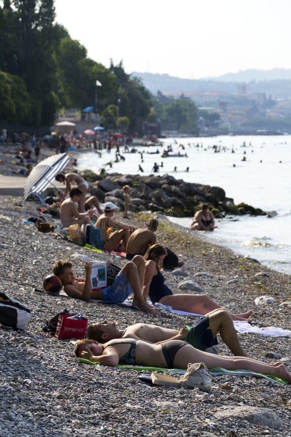 Povos que tomam sol na praia o 30 de julho de 2016 em Desenzano del Garda, Itália imagens de stock