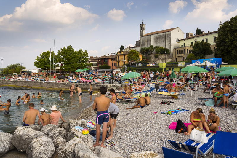 Povos que tomam sol na praia o 30 de julho de 2016 em Desenzano del Garda, Itália foto de stock royalty free