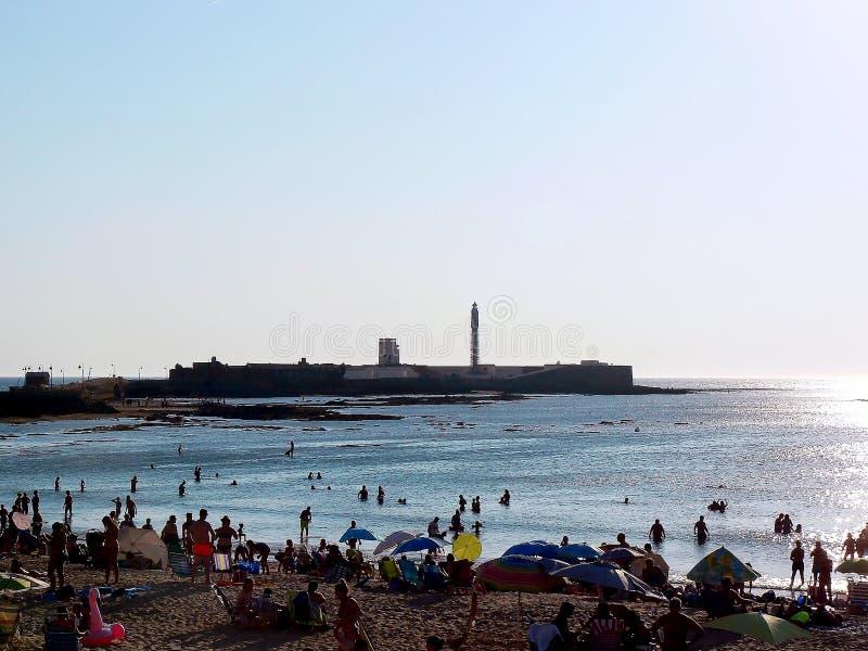 Povos que tomam sol no por do sol na praia do La Caleta na baía de Cadiz, a Andaluzia spain fotografia de stock