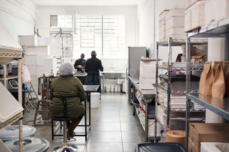 Povos que trabalham em uma fábrica artisanal pequena da fatura de chocolate foto de stock royalty free