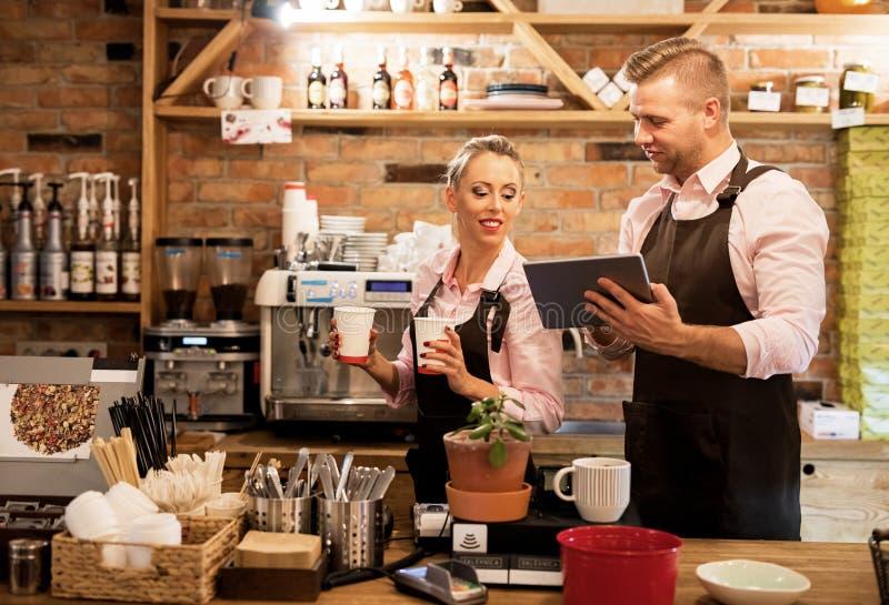 Povos que trabalham no café e que usam a tecnologia fotos de stock royalty free